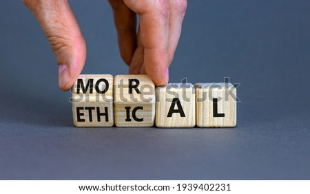 Ethical or moral symbol. Businessman turns wooden cubes and changes the word 'moral' to 'ethical' on a beautiful grey table, grey background. Business and ethical or moral concept. Copy space. ストックフォト ©