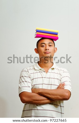 ethnic asian man with stack of books placed on head