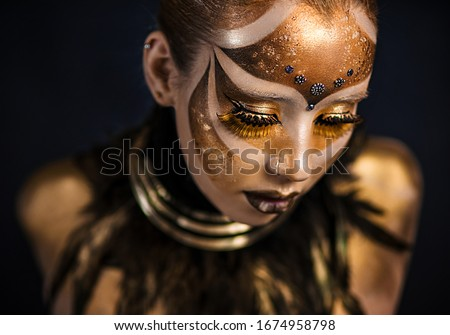 Ethnic body painting. Carnival mask. Golden statue. Keeper of the Sun tribe. Golden body. girl in gold paint. Fantasy makeup