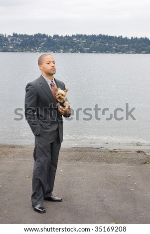 Ethnic Business Man and Yorkshire Terrier Dog are standing next to the lake. He is dressed in a suit and tie and seems to be contemplating something.
