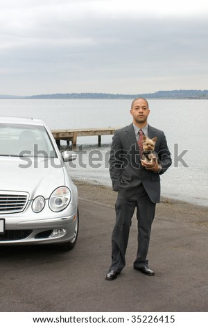 Ethnic Business Man and Yorkshire Terrier Dog are standing next to the lake. He is dressed in a suit and tie and is holding the dog.