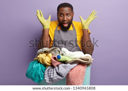 Ethnic emotional troubled man keeps hands spread near head, gestures actively and exclaims with negative emotions, stares at huge hamper of dirty laundry, doesnt know from what to begin first #1340965808
