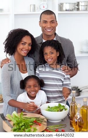 Ethnic family preparing salad together in the kitchen
