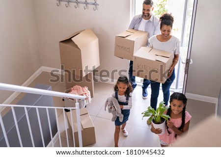 Ethnic family with two children carrying boxes and plant in new home on moving day. High angle view of happy smiling daughters helping mother and father with cardboard boxes in new house. Сток-фото ©