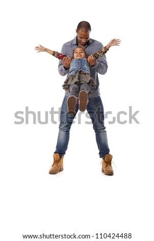 Ethnic father swinging little daughter between legs, playing, having fun, laughing.