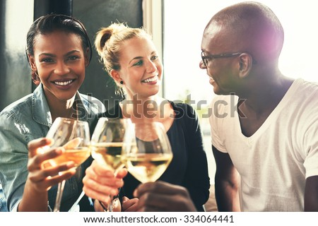 Ethnic friends drinking wine at a bar having a good time laughing Foto stock ©