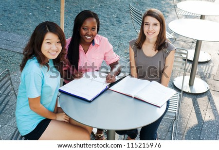 Ethnic group of girls outside studying and smiling