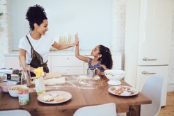 Ethnic joyful woman and excited adorable daughter enjoying cooking together and giving high five near messy kitchen table at home