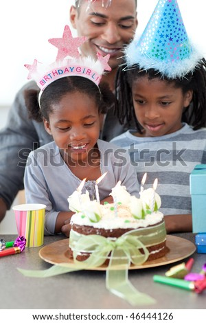 Ethnic little girl and her family celebrating her birthday in the kitchen