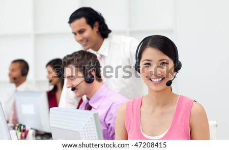 Ethnic manager checking his employee's work in a call center