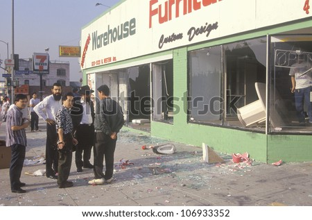 Ethnic men observing furniture store looted during 1992 riots, South Central Los Angeles, California
