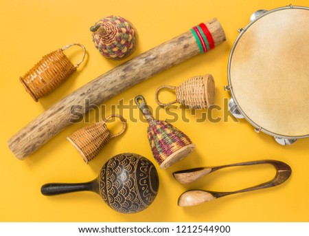 Ethnic percussion musical instruments on yellow background. Caxixi shakers, rainstick, pandeiro, maracas and musical spoons.  #1212544900