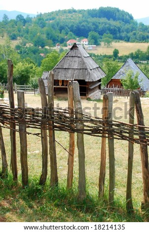Ethnic Serbia, wooden house behind fence over rural landscape