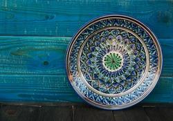 Ethnic Uzbek ceramic tableware on the blue wooden background. Decorative ceramic plate