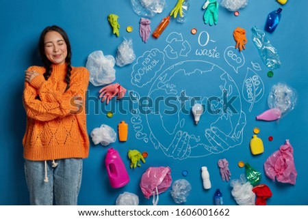 Ethnic woman embraces herself with love, dressed in casual clothes, enjoys pleasant thoughts, thinks about volunteering work, stands against blue wall with symbolic picture of planet and garbage