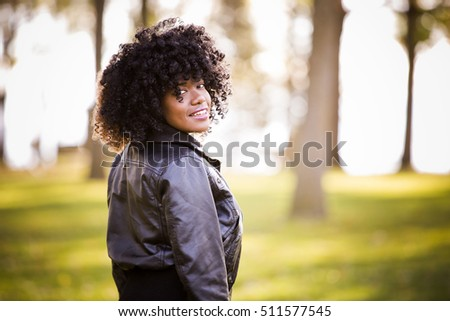 ethnic woman wearing fashion fall outfit outdoors int he park