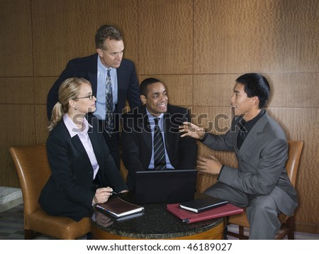 Ethnically diverse group of businessmen and a businesswoman having an enjoyable meeting together. Horizontal shot.