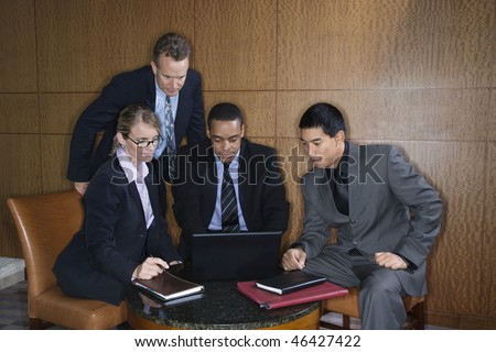 Ethnically diverse group of businessmen and a businesswoman look at a laptop computer screen. Horizontal shot.