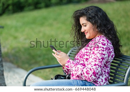 Ethnically diverse woman sitting on park bench on phone #669448048