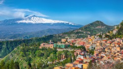 Etna volcano and Taormina town aerial panoramic view. Roofs of a lot of buldings. Smoking snow-capped Mount Etna volcano. Taormina, Sicily, Italy.