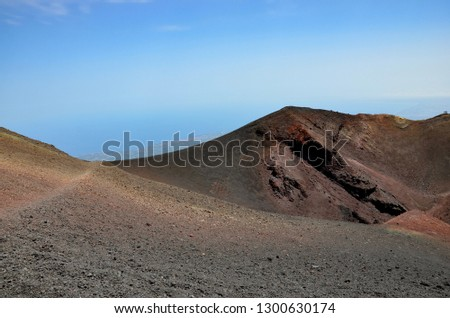 Etna volcano in Sicily, view from mountain to the mediterranean coast of the city of Catania, footpath on the left next to crater, hikers on the right, blue sky, sunny, summer #1300630174