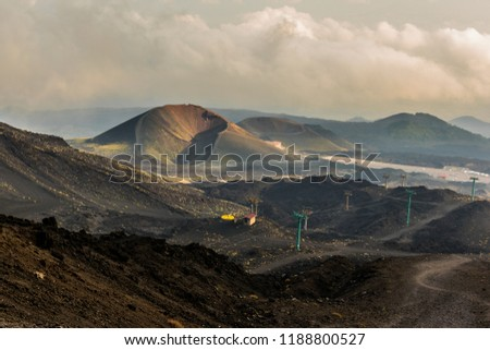 Etna volcano, Sicily, Italy. Mars-like or Moon-like mountain landscape. In the background two inactive craters, moguls, yellow sulfur coating, cable car, parking, sky with clouds.