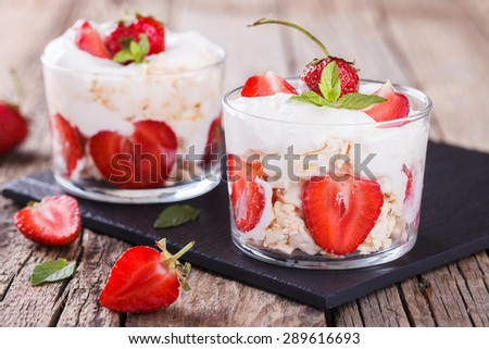 Eton Mess - Strawberries with whipped cream and meringue in a glass beaker. Classic British summer dessert.selective focus #289616693