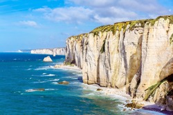 Etretat Aval cliff, rocks and natural arch landmark and blue ocean. Normandy, France, Europe.