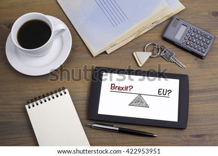 EU? and Brexit? referring to the upcoming EU referendum. Text on tablet device on a wooden table
