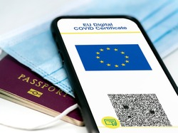 EU Digital COVID Certificate with the QR code on the screen of a mobile phone over a surgical mask and a passport. Immunity from Covid-19. Travel without restrictions.