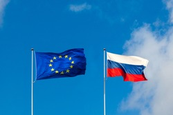 EU flag and Russia flag are on blue sky. Concept relations between Europe and Russia
