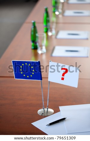 EU flag in a stand on table with second empty flag for your project and bottels with mineral water