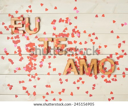 Eu Te Amo meaning I Love You in Portuguese written with the block letters covered with red heart shaped confetti over the wooden background Stockfoto ©