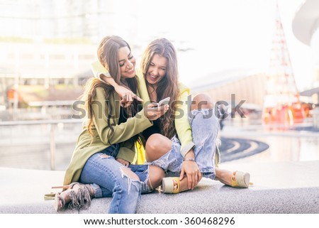 Euphoric friends watching videos on a smartphone and pointing at screen surprised - Girlfriends laughing and having fun outdoors