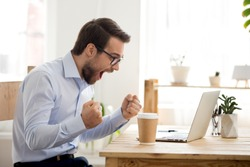 Euphoric happy businessman scream read good online news celebrating business success, great result watching game on laptop, excited by victory, betting win, professional achievement, feeling winner