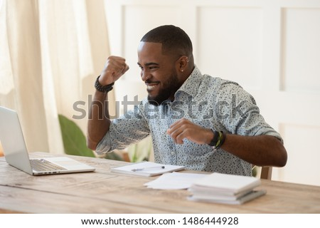 Euphoric young black man celebrating online lottery win, excellent educational online courses tests results, successful qualification training, getting remote dream work, received high paid job offer.