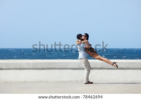 euphoric young couple meeting and hugging near the sea. Horizontal shape, side view, copy space