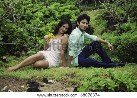 eurasian siblings lounging in a field in hawaii