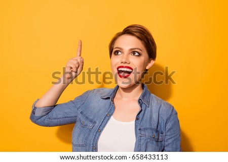Eureka! Cheerful attractive girl has an idea. She is wearing casual clothes, red pomade and pointing above with her finger