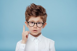 eureka, handsome little boy in glasses is surprised, inspired, I have an idea, Raise your index finger up, copy space, isolated on blue background