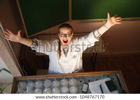 Eureka Happy female scientist lifting her hands in her laboratory. Inspiration ideas concept