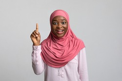 Eureka moment. Inspired young black lady in hijab pointing finger up, found solution for problem. African american muslim woman having creative idea, grey studio background, copy space