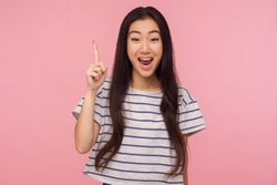 Eureka! Portrait of inspired girl with long hair in striped t-shirt pointing finger up with genius idea, surprised by suddenly invented smart solution. indoor studio shot isolated on pink background