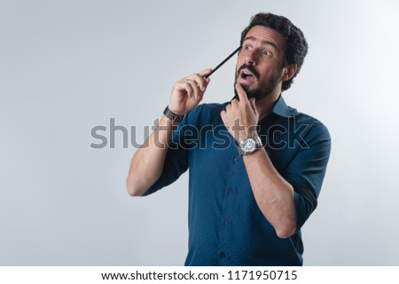 Eureka! Wondered creative guy having the best idea with pencil on his head, open mouth isolated against neutral background