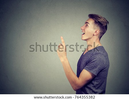 Eureka! Young man wearing casual denim shirt gesturing the idea with one finger up isolated on gray background