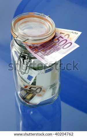 Euro bank notes in a glass jar on blue background - stock photo