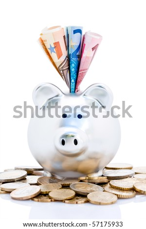 Euro bank notes in slot of piggy bank with pile of coins, isolated on white.