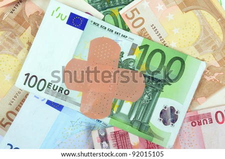 Euro bank notes with a band-aid - stock photo