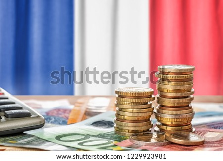 Euro banknotes and coins in front of the national flag of France #1229923981