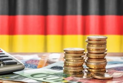 Euro banknotes and coins in front of the national flag of Germany